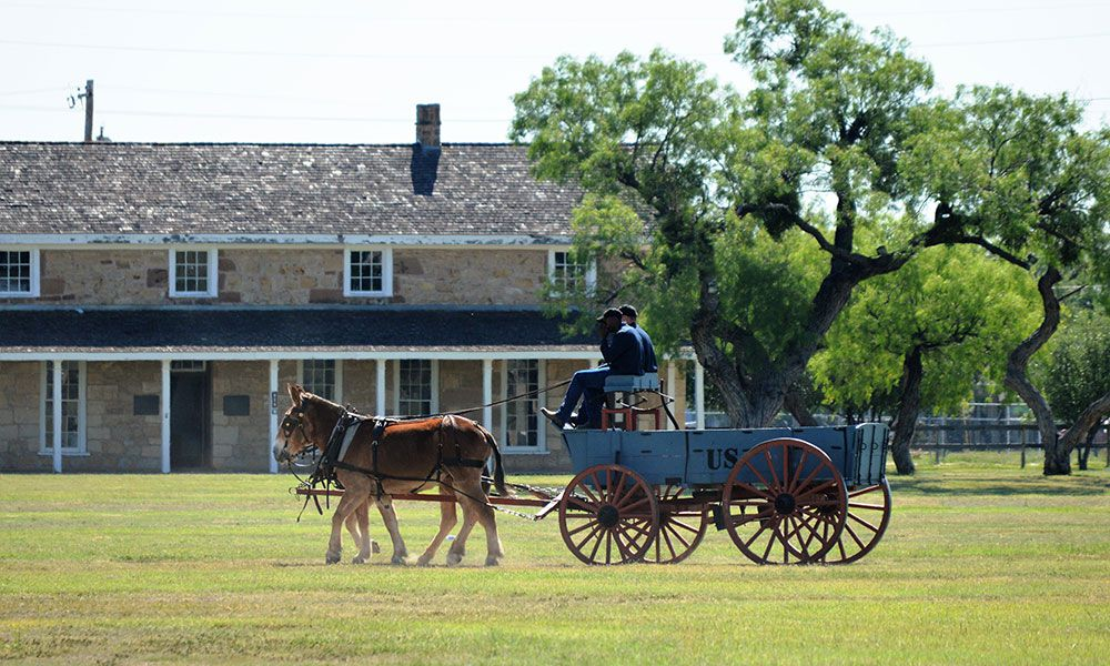 Stage coach with horses in front of building with trees