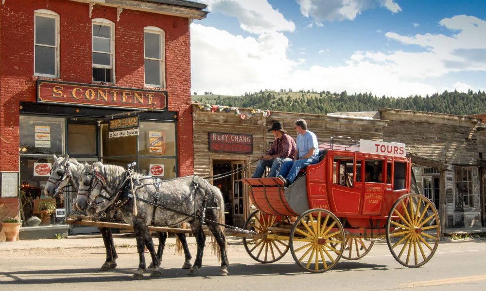 Stage coach in Southwest Montana with horses in front of old building