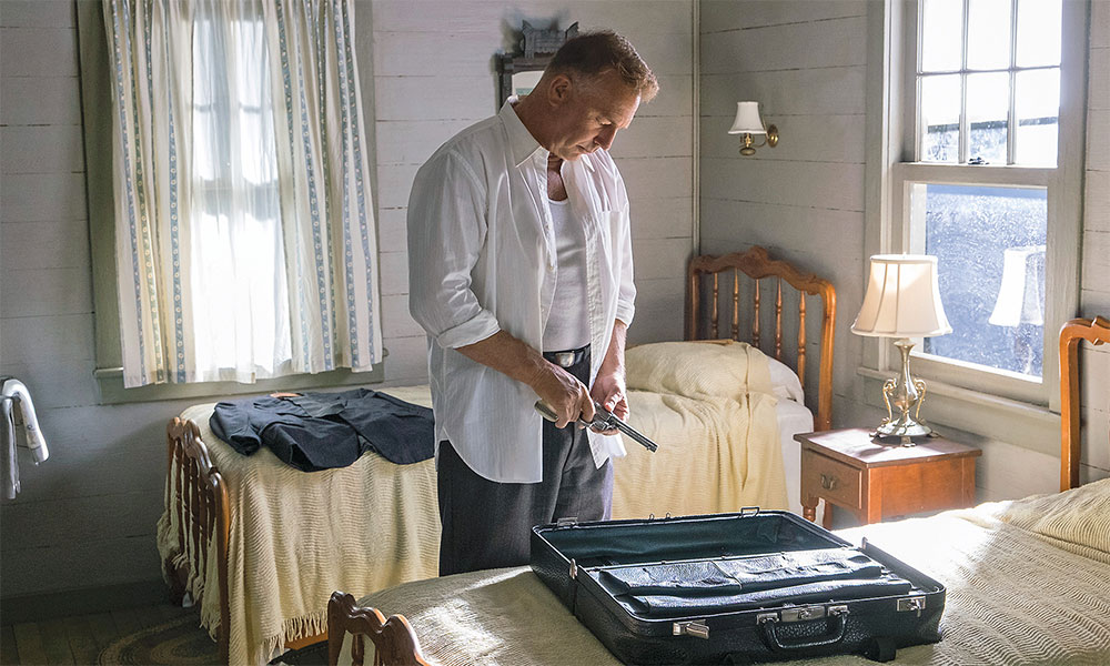 kevin costner in the highwaymen with a gun by a bed true west magazine