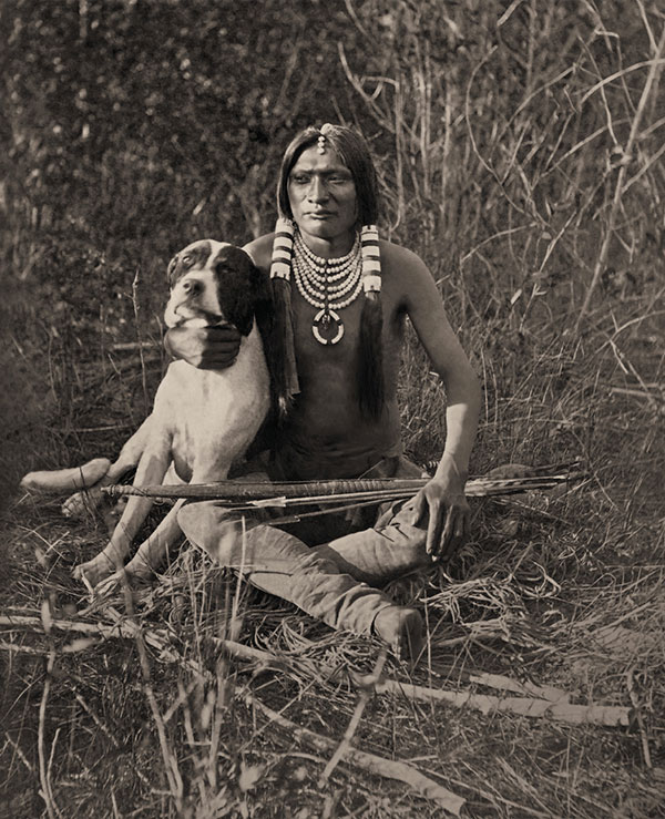 uinta ute boy and his dog in a field with arrows true west magazine