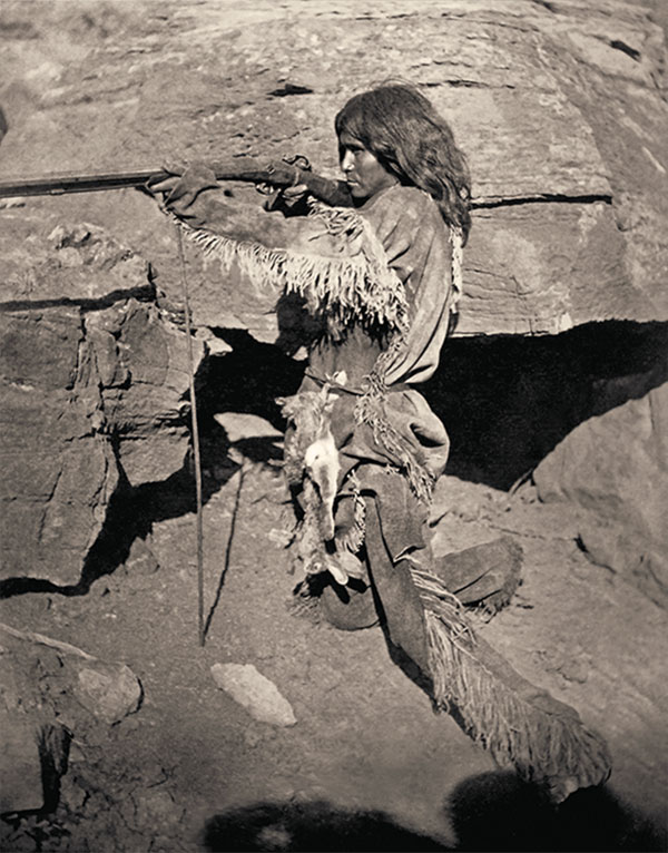 native american man with a gun on rocks true west magazine