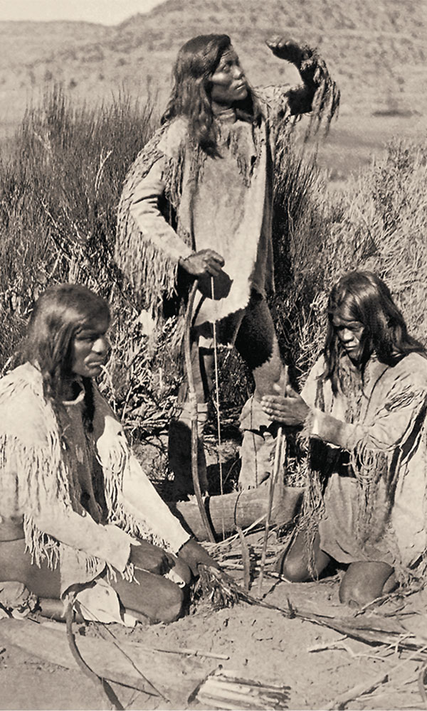 men kindling a fire by friction true west magazine