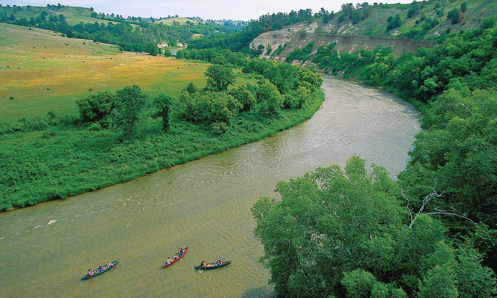 niobrara river valley with trees and kayaks true west magazine